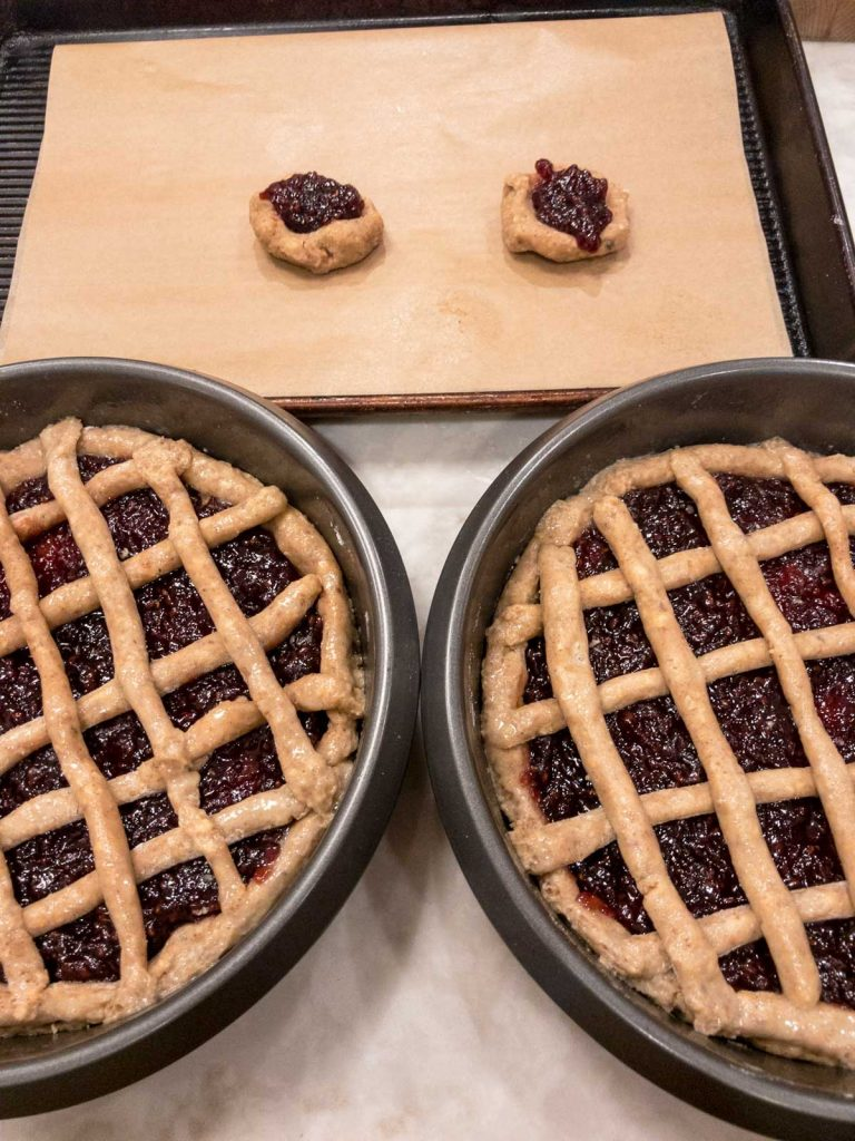 Two linzer torte in cake pans and cookies on a cutting board