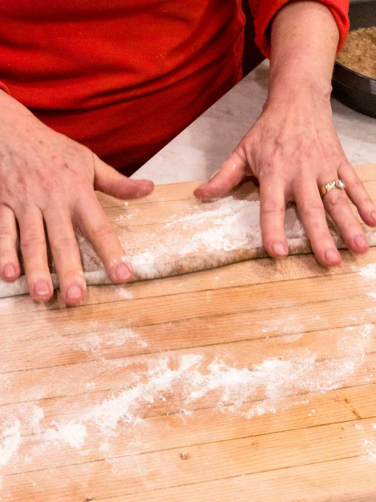 Hands rolling dough into a log on a cutting board