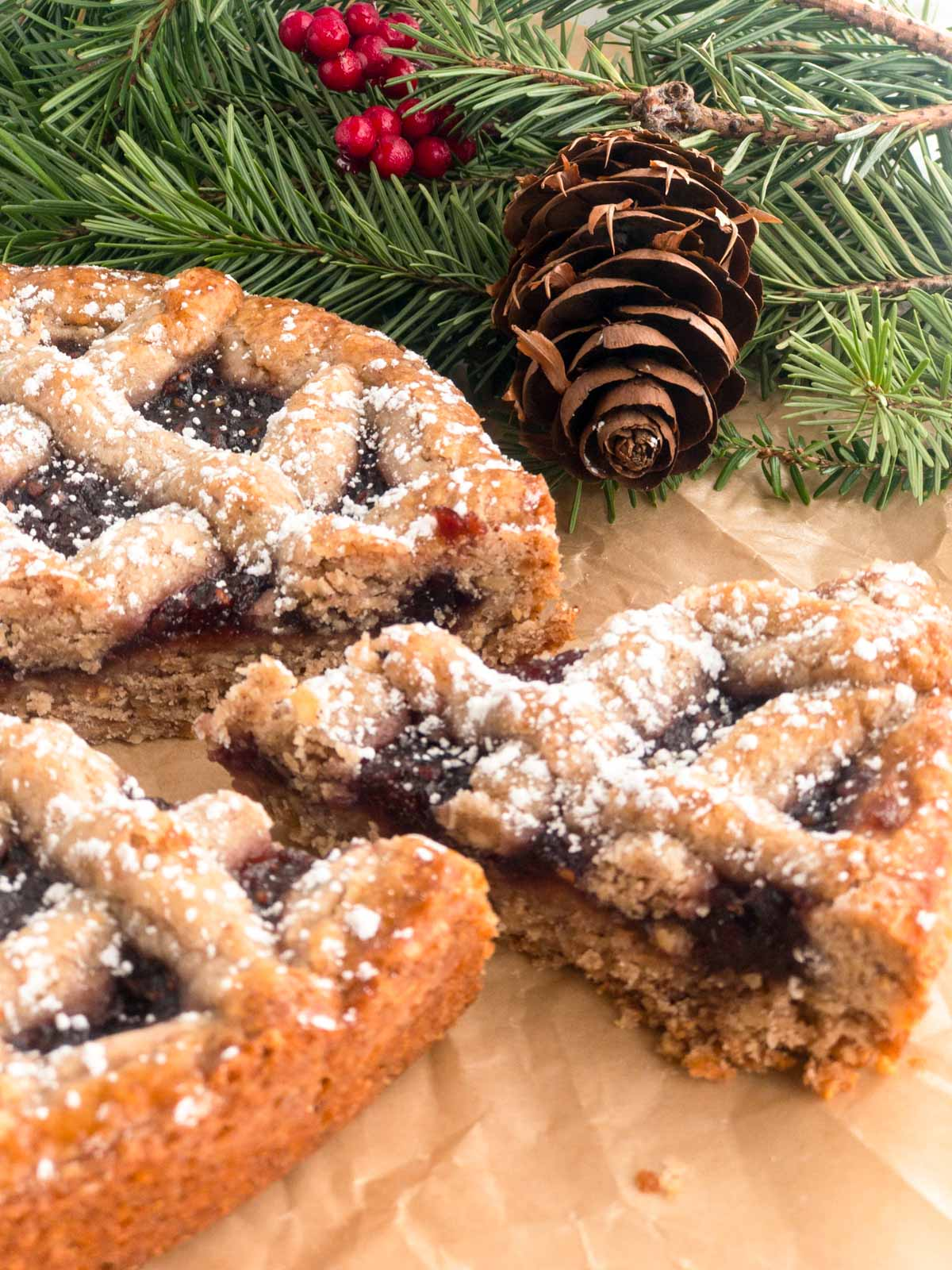 Linzer torte on brown parchment with pine cone and pine branch