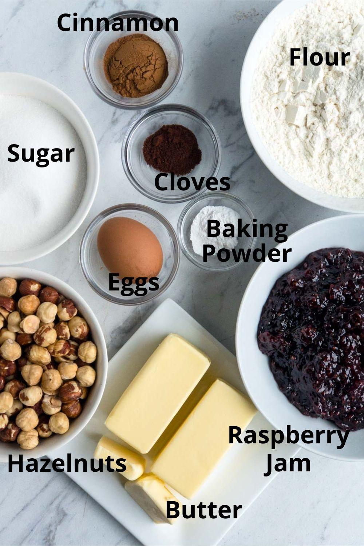 Butter, sugar, flour, hazelnuts, egg, cinnamon, cloves, baking powder, and raspberry jam on white surface