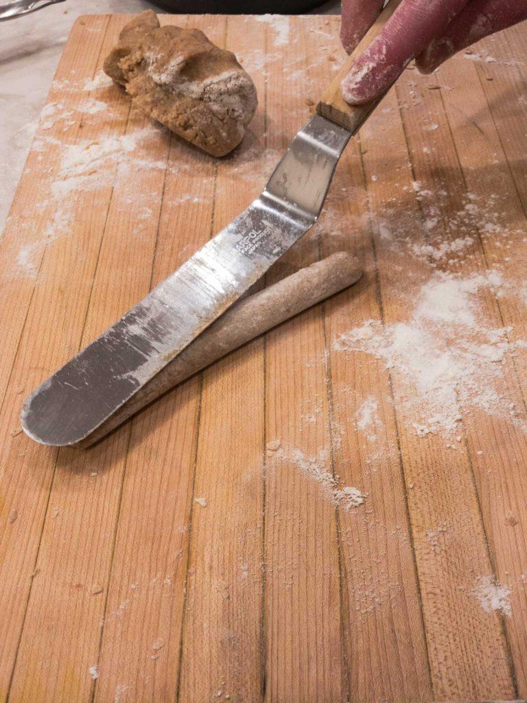 Spatula rolling dough into log on cutting board