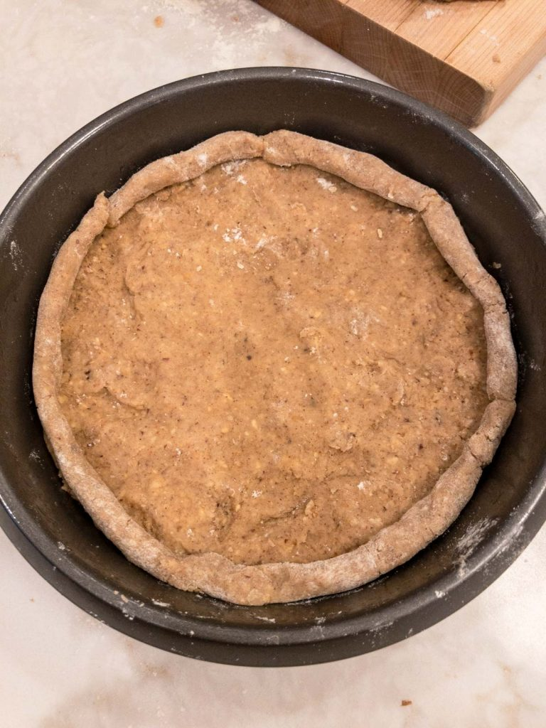 Linzer torte in a cake pan with base and crust edge