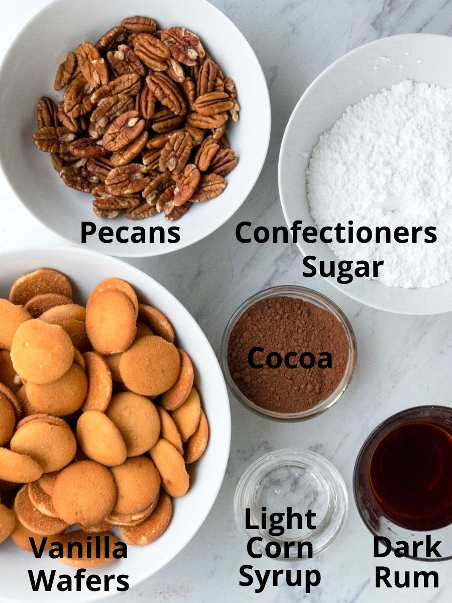 Rum ball ingredients, whole pecans, vanilla wafers, confectioners sugar, cocoa, rum, corn syrup all in individual bowls