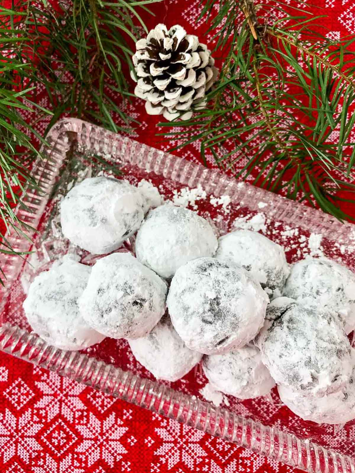 Rum balls on glass tray on red snowflake cloth with white pine cone and pine tree branch