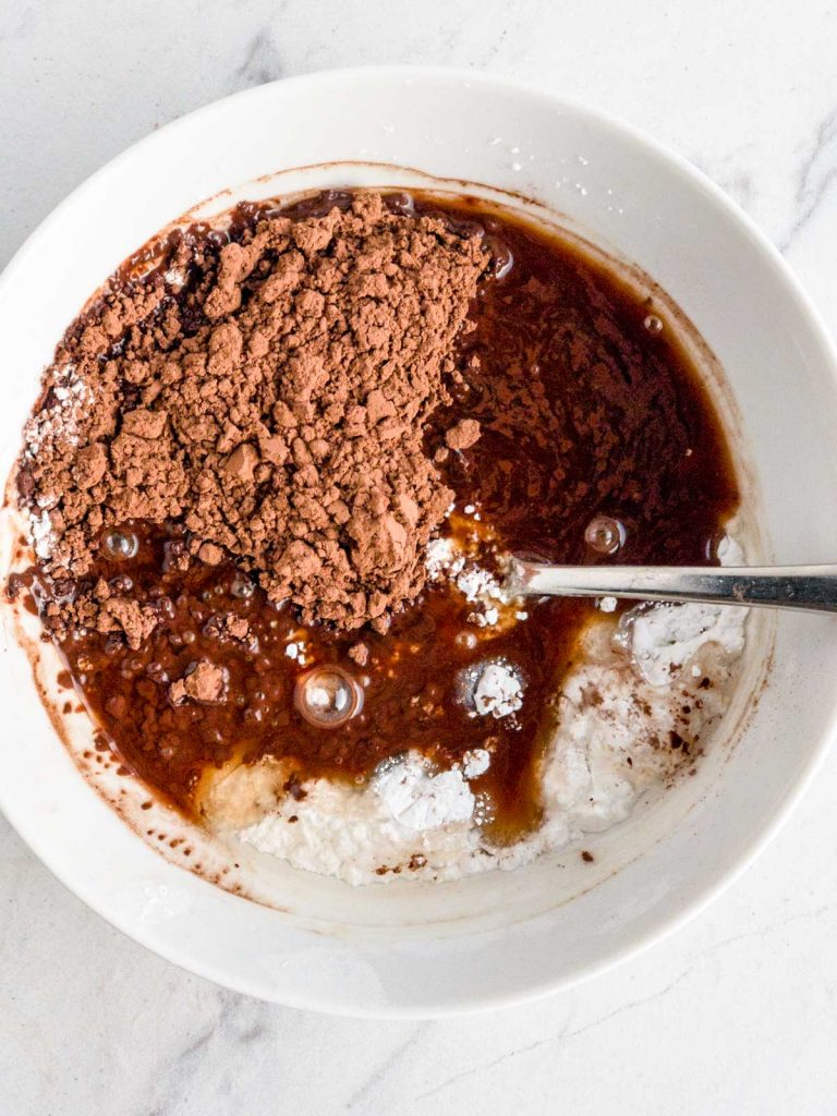 Rum, powdered sugar, cocoa and corn syrup in a white bowl with a silver spoon