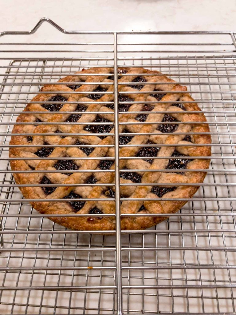 linzer torte on a cooling rack and a cooling rack on top of the pastry