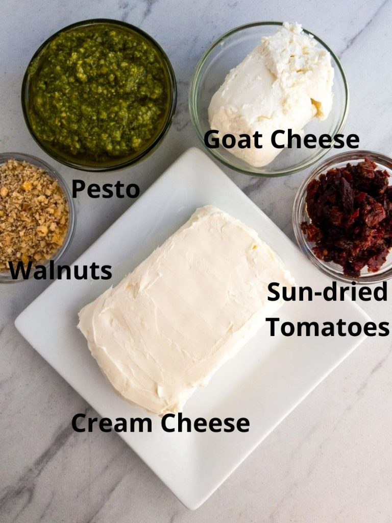 Cream cheese on a plate, sun-dried tomatoes in a bowl, pesto in bowl, finely chopped walnuts in a bowl, goat cheese in a bolw