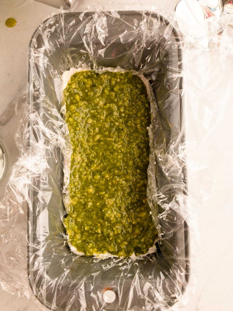 Pesto on cream cheese mixture in a loaf pan