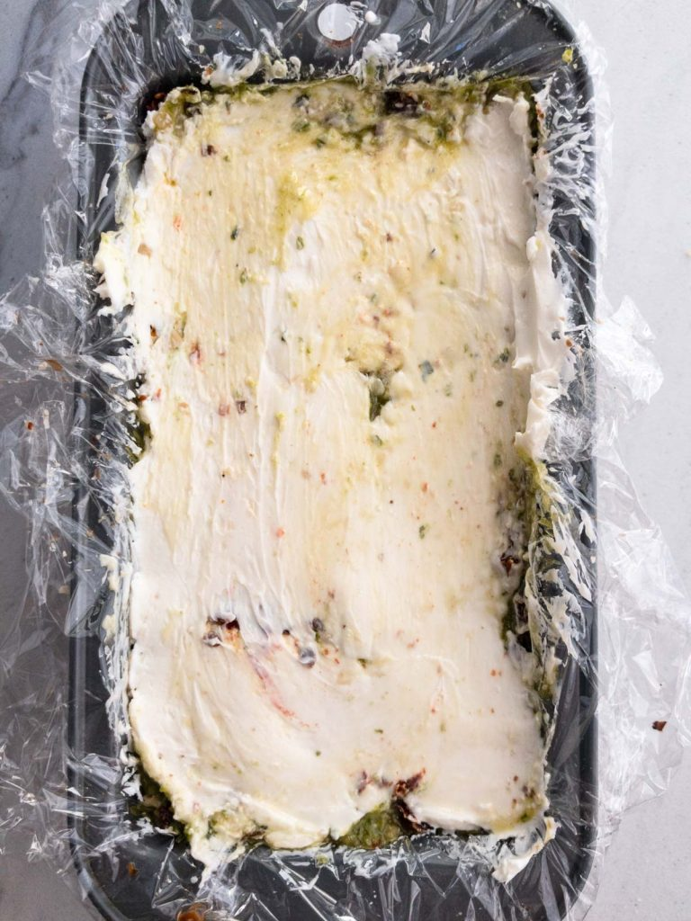 pesto spread in loaf pan with plastic wrap