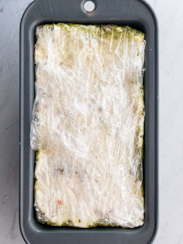 pesto spread in loaf pan covered in plastic wrap