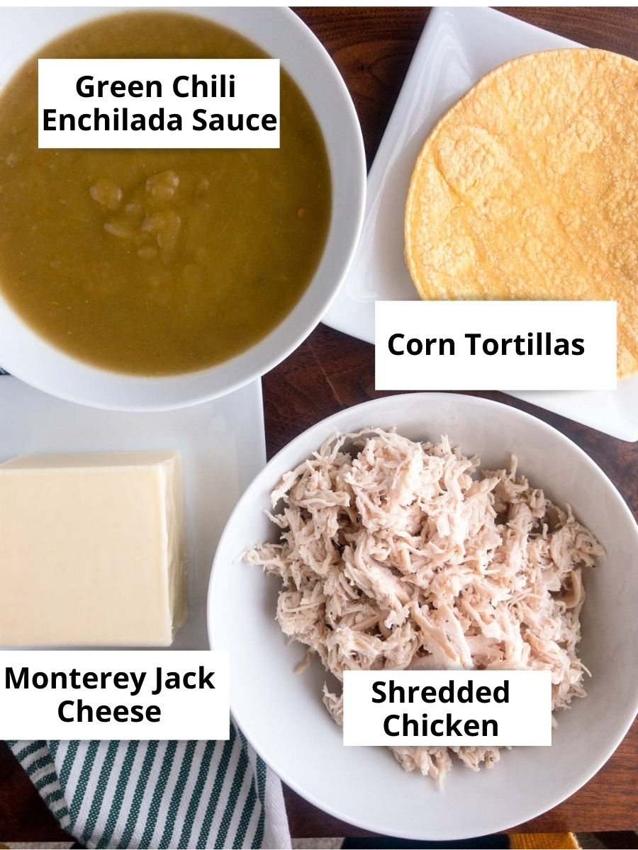 Green chili enchilada sauce in a white bowl, corn tortillas, block of Monterrey Jack Cheese, Shredded Chicken in a white bolw